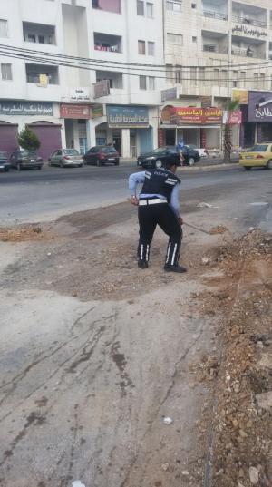 شرطي سير يردم حفرية مكشوفة تركها مقاول! (صور)